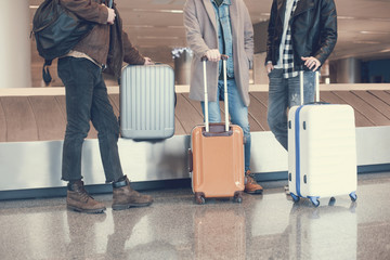 Three men situating near luggages while waiting for plane in hall. Expectation and tourism concept