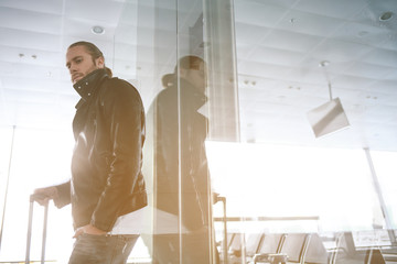 Low angle portrait of pensive bearded man leaning on window while standing in airport. Copy space. Trip concept
