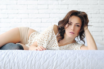 Девушка в белом интерьере. Девушка на кровати лежит дома. Девушка на матрасе. Кровать на полу. Белый кирпич в интерьере. Утро милой девушки. Светлый интерьер дома.