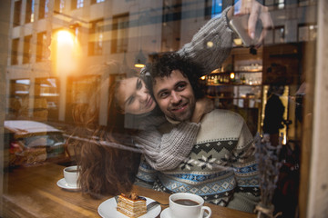 Portrait of happy loving couple making selfie on smartphone and smiling. They are hugging in cafeteria near window