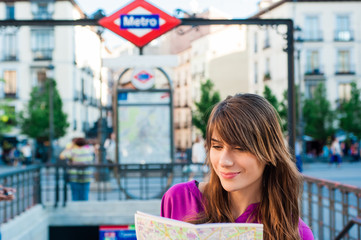 Young tourist woman in front of Madrid, metro station.