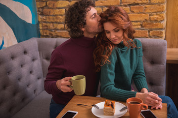 Affectionate young man is kissing woman with gentleness. He is sitting at table in cafe and holding cup of coffee