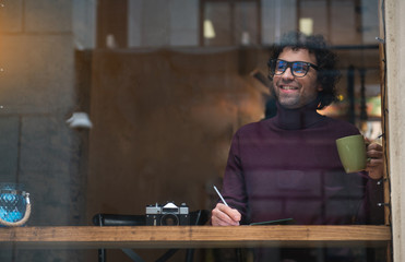 Portrait of happy guy making notes in his notepad. He is drinking cup of tea and smiling. Inspiration concept. Copy space
