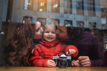 Portrait of happy man and woman kissing their little daughter in cheek with love. Girl is smiling while holding photo camera