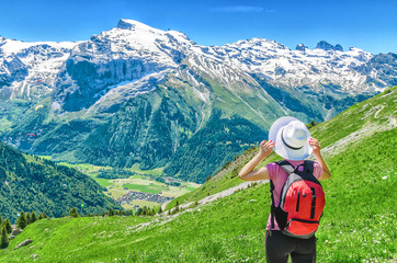 Swiss Alps. A girl in a white hat and a red backpack admiring the panoramic view of the Alpine mountains. Landscape of the Swiss Alps, the Engelberg resort.