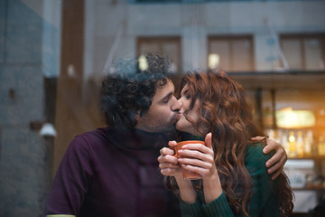 Happy loving couple kissing with gentleness. They are embracing while girl is holding mug of hot coffee. View from the glass window