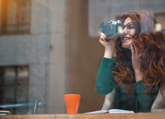 Excited female photographer using camera and laughing. Lady is sitting in cozy cafeteria. Copy space