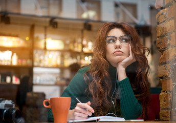 Portrait of serious girl planning her day. She is making notes and looking up pensively while relaxing in cafeteria. Copy space