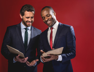 Business plan. Cheerful young elegant entrepreneurs are standing together with folders and talking with smile. Isolated on red background