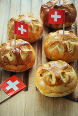 Celebrating Switzerland National Day on August 1st with traditional symbols like swiss flag red with white cross. Special bread buns with cross shape cut. Red berry sauce with  white cross.