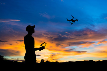 silhouette of man controlling the flying drone to recording video at sunset