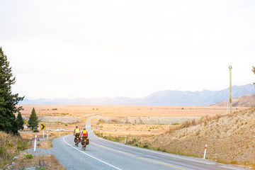 A couple of travelling cycling on the way traveling around in South Island, New Zealand