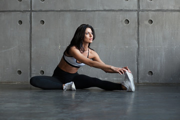 athletic brunette woman stretching legs