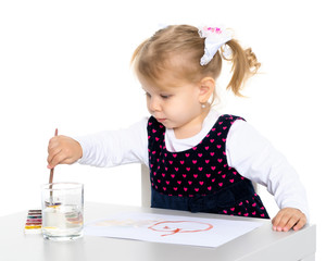 A little girl is drawing at the table.