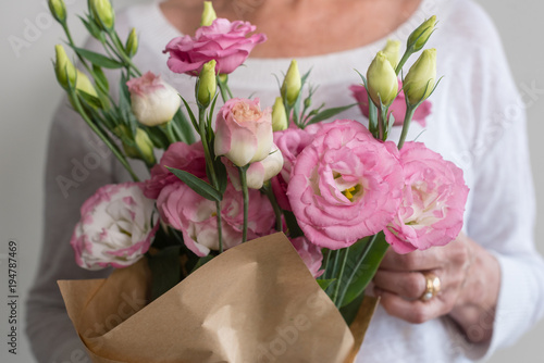 Close Up Of Woman Holding Bouquet Of Pink Lisianthus Flowers Wrapped