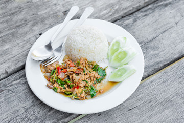 Rice topped with stir-fried minced pork the popular of favorite delicious local Thai food for all meals every day on wooden table