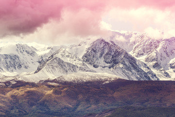 Foto auf Leinwand Rosa hell The peaks of the snowy mountain range under the pink sky. Landscape rocks in pastel color.