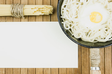 Pan with spaghetti and scrambled eggs on a wooden table. Bundle of dry spaghetti, the cooking. Copy space for text