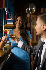 Young couple having fun night out drinking cocktails at the bar