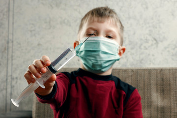 Portrait of a boy, a child in a medical mask is holding a syringe in his hands. The concept of disease, flu in children, tuberculosis, immunity, protection from disease.
