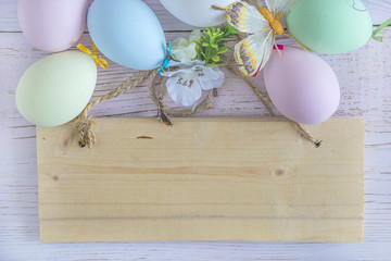 Easter greeting card with pastel colored eggs and decoration on wooden background