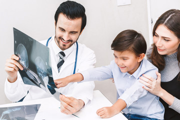Doctor showing the X-ray photo to little boy in hospital.healthcare and medicine