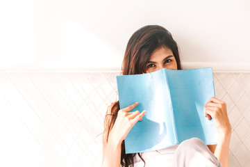 Woman reading book on bed in the morning