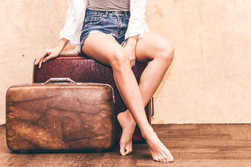 Beautiful traveler woman sit on vintage brown traveling luggage suitcase with wall background