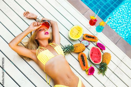 Beautiful sexy blonde girl in pool at hotel. Yellow swimsuit glasses tropical fruit papaya watermelon pineapple, summer vacation, smiling, close-up on top, blue water, slender figure