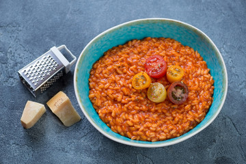 Plate with tomato risotto and parmesan cheese on a blue stone background, studio shot
