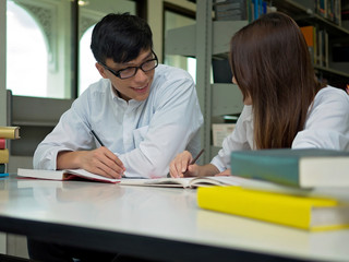 sian university life concept. Young teenage student reading book in college library.Couple Student in the Library of College.Education Concept.In selective Focus