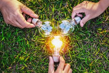 group hand holding lightbulb with sunset on grass. concept idea solar energy