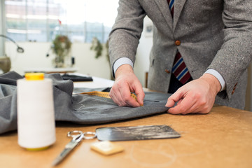 Tailor working with jacket in workshop