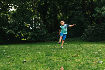 Chinese American boy skipping towards camera in grassy park