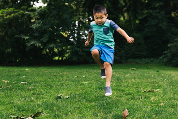 Asian American preschooler skipping in grass at park