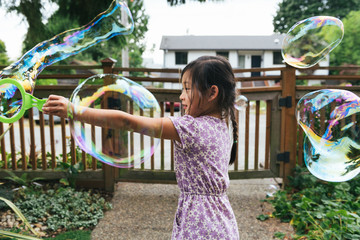 Asian American girl making bubbles outside with bubble wand