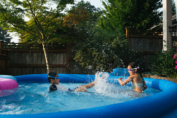 Asian siblings splashing each other in inflatable outdoor pool