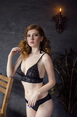 Young beautiful redhead woman in lace lingerie jn the black wall baackground. Retro style sexy lady  in black underwear