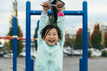 Asian elementary school girl hangs from play structure while smiling