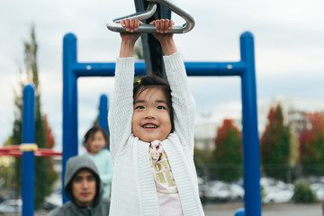 Asian girl playing on zip line on playground