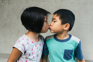 Boy girl fraternal twin young children kissing on the lips