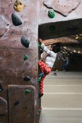 Vertical image of little Asian American girl bouldering inside indoor rock climbing gym