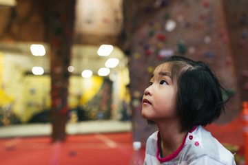 Close up portrait of little Asian American girl observing activity at indoor rock climbing gym