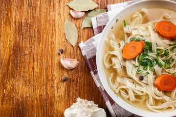 Tasty meat broth with noodles, carror and parsley