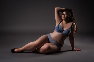 Plus size sexy model in underwear, fat woman on gray background, overweight female body