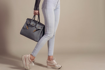 Shopping concept.girl in jeans and sneakers holds a fashionable big bag closeup with copy space.