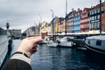 Tourist holding a piece of national bank bill towards the Nyhavn boats