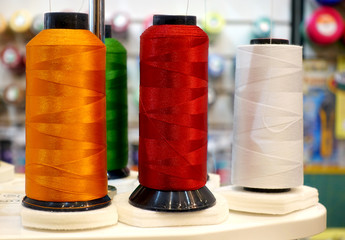 Sewing industry. Color coils of thread on holders.