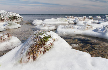 The frozen rocky beach of the sea. Stones covered with ice. Ice landscape.