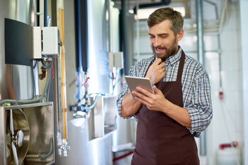 Portrait of smiling bearded technician wearing checked shirt and apron using digital tablet while adjusting equipment at modern brewery